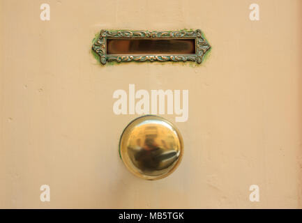 Old brass mail letter box and door knob on a yellow front door - Stock Photo