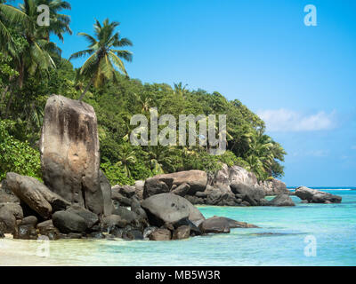 A rocky formation on a Seychelles beach with blue skies - Stock Photo
