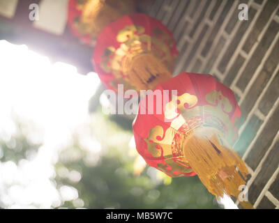 Chinese paper lanterns with light bleed on a grey brick archway with engraved wood in the Seychelles - Stock Photo