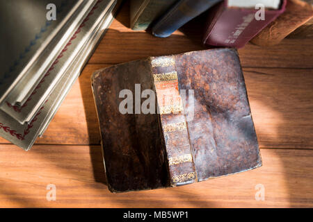 Detail photograph of an old book opened on wooden boards in which the texture of the cover can be seen with a stack of books in the background. - Stock Photo