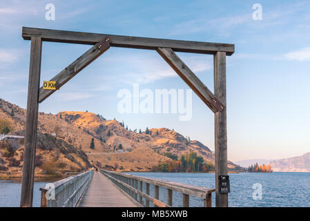 Wood archway over former train trestle bridge converted to walking and biking trail with lake and mountains in distance at sunset - Stock Photo