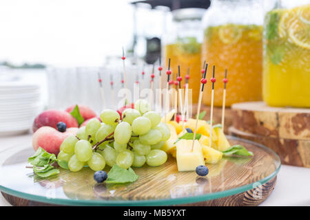 fruit plate. Glass bank of lemonade with sliced citrus fruits on a buffet table. Summer party outdoor. Detox. - Stock Photo