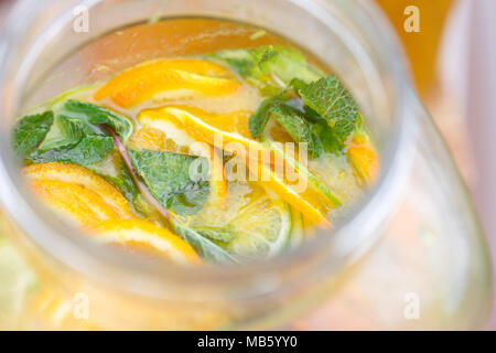 Glass bank of lemonade with sliced citrus fruits on a buffet table. Summer party outdoor. Detox. - Stock Photo