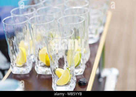 Glass for lemonade with sliced citrus fruits on a buffet table. Summer party outdoor. Detox. - Stock Photo