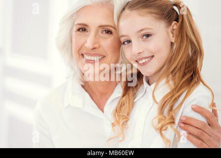 Loving grandmother embracing her granddaughter sitting on lap - Stock Photo