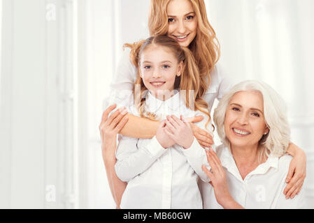 Beautiful lady hugging her daughter and mom with love - Stock Photo