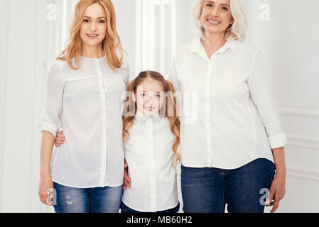 Family shot of three generations of woman posing together - Stock Photo