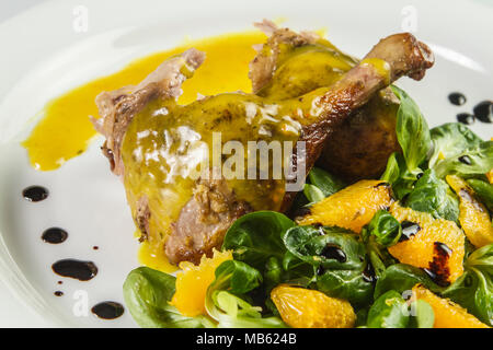 Duck legs with orange sauce and lamb's lettuce salad with oranges and vinegar. - Stock Photo