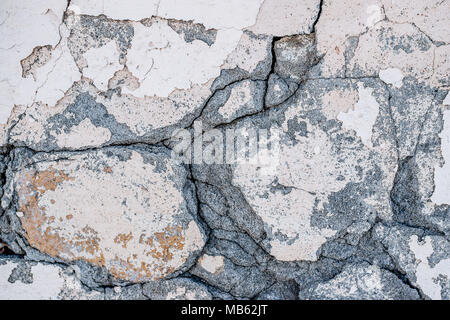 Background of natural cement plaster on the wall grey plain textured with cracks and brick in the upper right corner. The horizontal frame. - Stock Photo