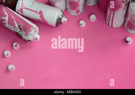 Some used pink aerosol spray cans and nozzles with paint drips lies on a blanket of soft and furry light pink fleece fabric. Classic female design col - Stock Photo