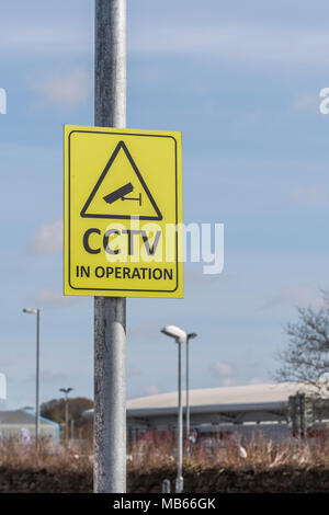 CCTV security camera in operation yellow warning sign - Watching over You, surveillance / Orwellian / Big Brother / intelligence gathering concepts. - Stock Photo