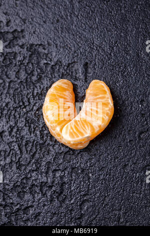 The mandarin slices are lined in the shape of a heart on a black background. - Stock Photo
