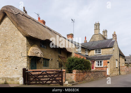 A view of the main street in the pretty village of Ravenstone, Buckinghamshire, UK; with thatched and stone built properties lining. - Stock Photo