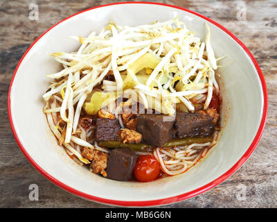 Traditional Rice Noodles Soup with Chicken Blood, Sliced Tomatoes and Dried Chilies - Stock Photo