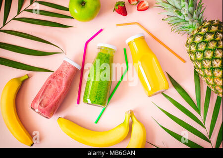 Flat-lay of colorful smoothies in bottles with fresh fruits and on pink  background, top view. Natural Organic Food Style. - Stock Photo