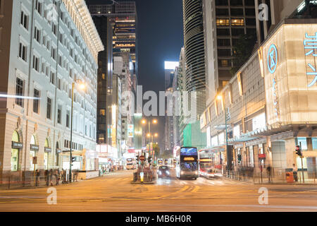 KOWLOON HONG KONG, SEPTEMBER 20, 2017; Buses nad cars in night-time long exposure of passing vehicles on busy city intersection of Nathan and Salisbur - Stock Photo