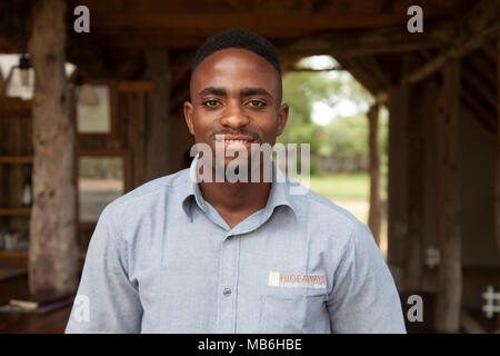 Staff member at the Elephant Eye Safari Lodge in Hwange National Park, Zimbabwe. The man is a server at the resort. - Stock Photo