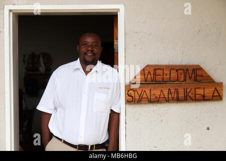 Staff member at the Elephant Eye Safari Lodge in Hwange National Park, Zimbabwe. The man leans against a door frame by a sign welcoming guests. - Stock Photo