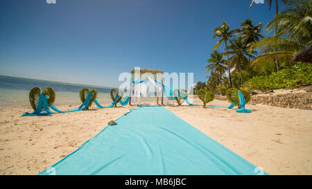 A wedding arch decorated with flowers and large wind-developing fabrics on a tropical beach. Philippines. Bohol. - Stock Photo