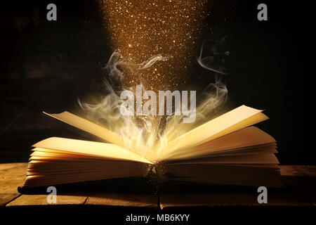 image of open antique book over wooden table - Stock Photo