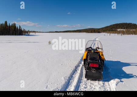 Snowmobile on a track on a frozen morass with a mountain and a blue sky in background, picture from the Northern Sweden. - Stock Photo