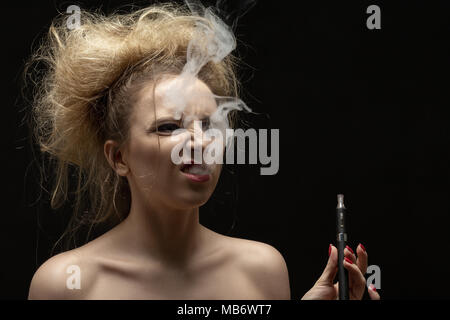 young woman smoking electronic cigarette on black background - Stock Photo
