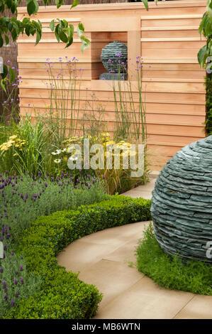 Original spherical stone centrepiece sculptures, path & medicinal plants - 'Embracing Tranquility' garden, RHS Flower Show, Tatton Park,  England, UK. - Stock Photo