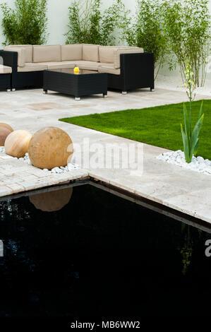Minimalist & contemporary, 'Breathe' show garden with stylish patio, seating area, pond & stone spheres - RHS Flower Show, Tatton Park,  England, UK. - Stock Photo