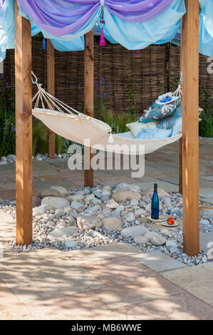 Cosy hammock under shade of pergola on patio for summer relaxation -  'Dreams Just Dreams' show garden, RHS Flower Show, Tatton Park,  England, UK. - Stock Photo