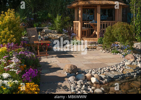 Beautiful spot to rest (summerhouse, seating, stream & bright flowers) - 'Water Way to Go ' rock garden, RHS Flower Show, Tatton Park,  England, UK. - Stock Photo