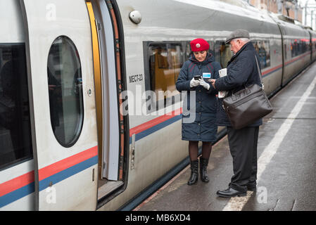 Train conductor (red beret, jacket) of Sapsan train checks in passenger using electronic device at Moskovsky railway station, Saint Petersburg, Russia - Stock Photo