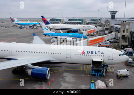 Delta and KLM aircraft on the runway awaiting departure at Amsterdam Schiphol Airport. - Stock Photo