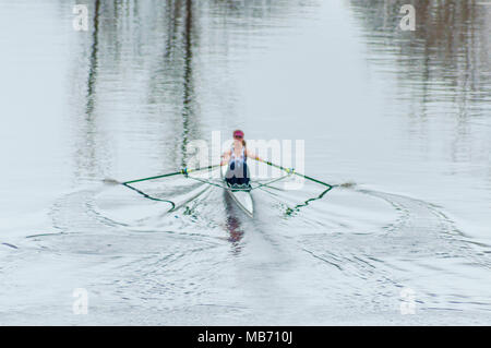 Glasgow, Scotland, UK. 7th April, 2018. UK Weather. Female rower from the Strathclyde  University Boat Club, SUBC, in a single scull training on a calm River Clyde on a wet  afternoon. Credit: Skully/Alamy Live News - Stock Photo