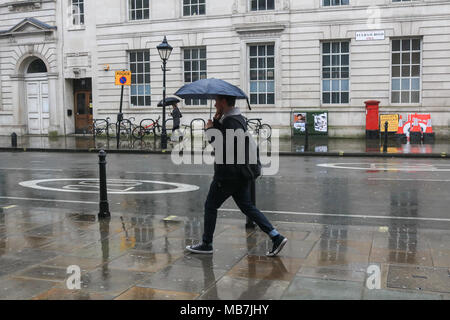 London UK. 8th April 2018. Pedestrians shelter from the  wet conditions on Fulham road as the rains arrive after sunny spells Credit: amer ghazzal/Alamy Live News - Stock Photo