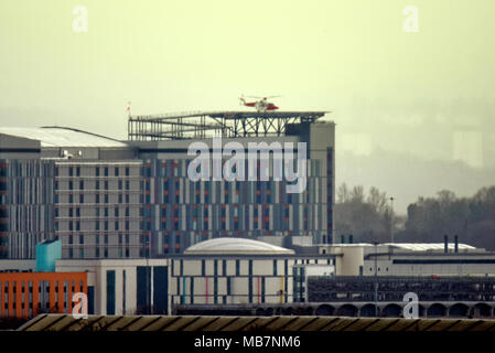 Glasgow, Scotland, UK 8th April. UK Weather: Emergency medical helicopter lands at the Queen Elizabeth University Hospital known locally as the death star because of its helipad in Govan on a miserable wet day with squalid showers. Gerard Ferry/Alamy news - Stock Photo