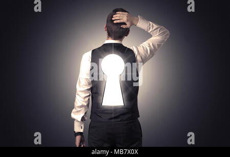 Young businessman standing and thinking with black keyhole on his back - Stock Photo