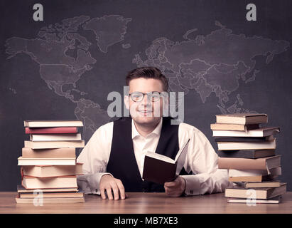 A young ambitious geography teacher in glasses sitting at classroom a young ambitious geography teacher in glasses sitting at classroom desk with pile of books in gumiabroncs Gallery