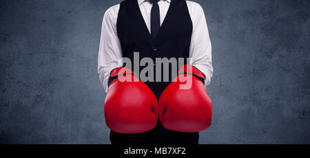 A well dressed sales person standing with red boxing gloves on his hand in front of urban grey wall background concept. - Stock Photo