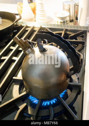 Alessi Richard Sapper kettle with melodic whistle boiling water on a gas top stove - Stock Photo