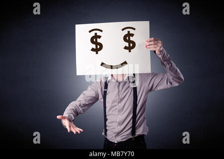 Young casual businessman hiding behind a greedy face drawing on cardboard - Stock Photo