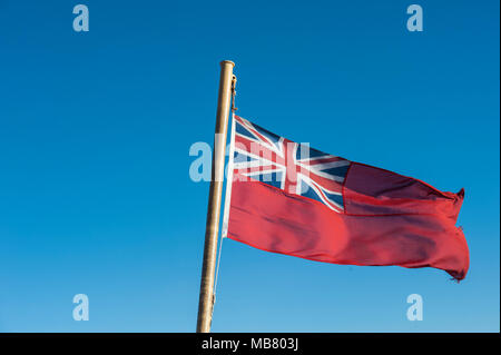 A Royal Ensign flag flies on the stern of a ship in Scotland - Stock Photo