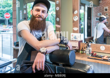 Portrait of a confident young barber smiling in a vintage beauty salon - Stock Photo