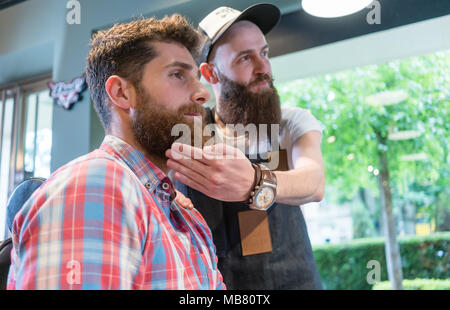 Bearded young man thinking of a trendy change of look in the hair salon - Stock Photo