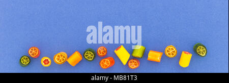 Assortment of colorful sweet handmade candy pieces arranged on blue paper - Stock Photo