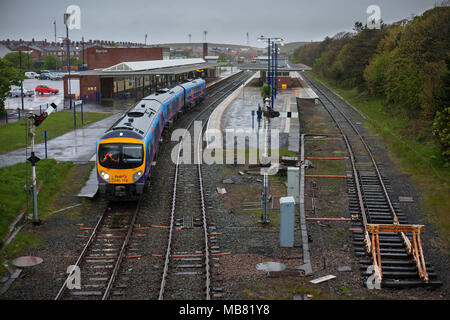 A First Transpennine express class 185 train departing from  Barrow In Furness railway station in the rain - Stock Photo