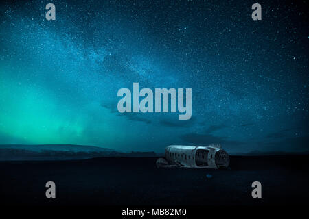 DC-3 plane wreck at night with milky way and northern light aka aurora borealis on the sky - Stock Photo