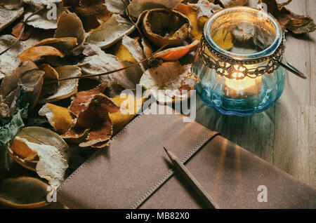 notebook and a vintage candle lantern with dried fruit peel - Stock Photo