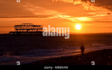 Brighton, United Kingdom - March 27 2018:   Man watching the sunset behind the ruins of West Pier on Brighton beach - Stock Photo