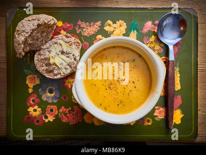A rustic bowl of thick soup and spoon with a buttered wholemeal bread roll - Stock Photo
