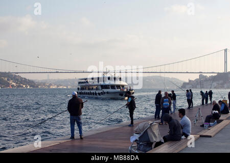 View of fishermen, ferry boat and FSM bridge in Istanbul. - Stock Photo